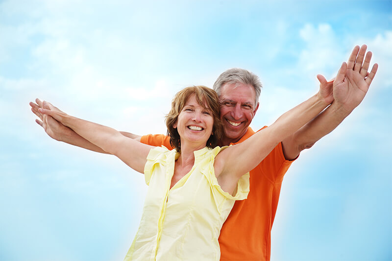 Pure Hcg Midlife Couple With Arms Outstretched Smiling